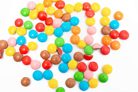 A lot of multi-colored small round candy pills are scattered on a white background, top view
