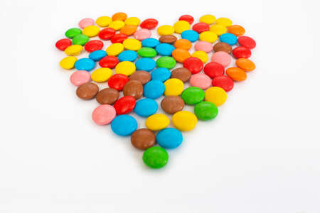 Multicolored round jelly beans collected in the form of a heart on a white background. Reklamní fotografie