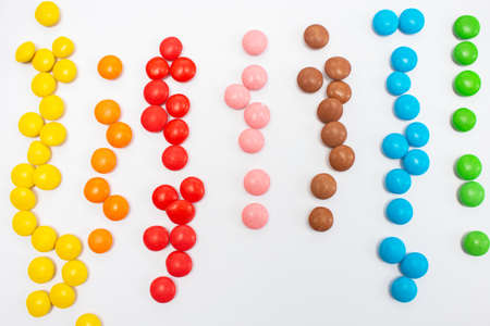Multi-colored little jelly beans sweets laid out in line colors