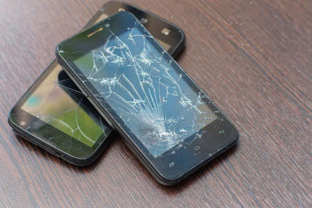 Two broken black smartphones lie the friend on the friend on a wooden background