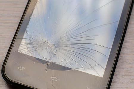 Part of the broken phone screen. Cracks on smartphone glass.