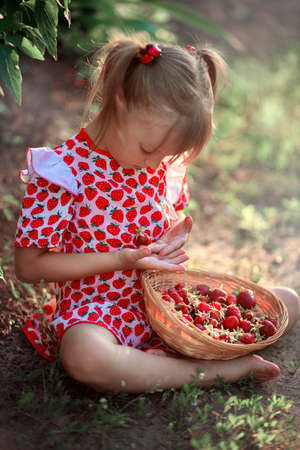 A little girl in a dress with a drawing of strawberries sits in a clearing and holds strawberry in her hands