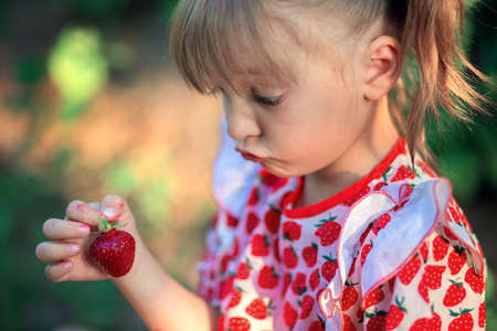 A little girl looks in surprise at a strawberry in her hands. The child makes faces.