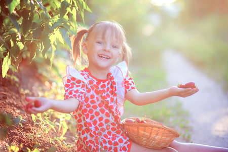 Happy smiling girl in a summer dress sits on the ground in the village and holds strawberry berries in her hands