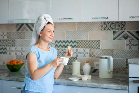 Happy Girl with a towel on her head sutra drinks coffee with cookies for breakfast in his own kitchen