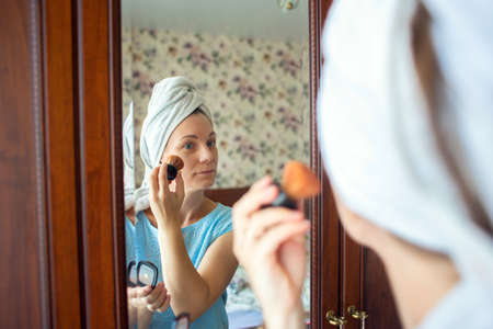 A woman with a washed head in a towel does makeup in her bedroom in the morning. Girl puts a blush on her cheeks with a brush Reklamní fotografie