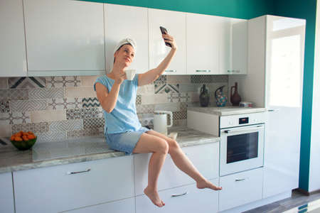A woman with a towel on her head after a shower sits in her kitchen with a cup of coffee or tea and photographs herself on a smartphone.