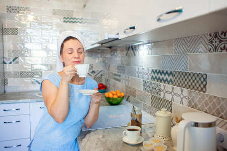 A woman washed her hair in the morning and drinks coffee with a towel on her head. Morning toilet and breakfast in the kitchen