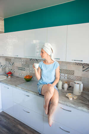 A girl with a towel on her head sits on the table in her kitchen and drinks coffee