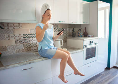 Woman with a towel on her head in her kitchen having breakfast and looking at the phone Stok Fotoğraf