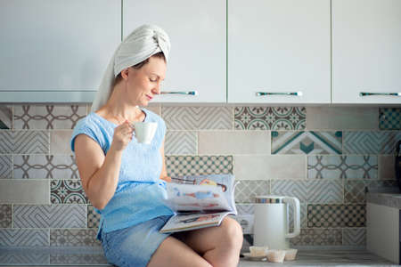 A girl with a towel on her head in her kitchen drinks coffee and leafs through a magazine