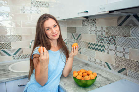 A girl with long hair in her kitchen picks ripe apricots