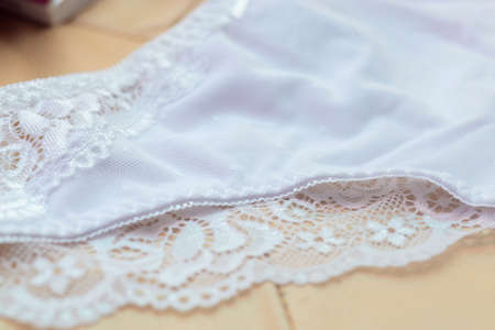 Lace on white womens bikini panties close-up. Delicate texture of the fabric of womens underwear