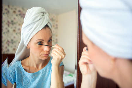 A woman with a washed head in a towel does makeup in her bedroom in the morning. Girl paints eyelashes with mascara