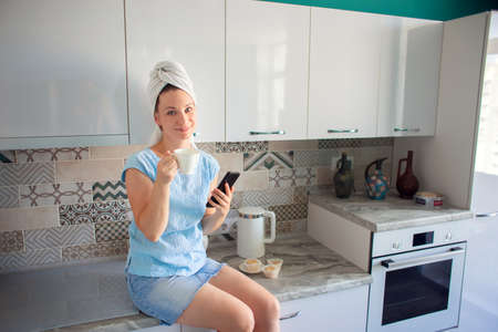 A girl with a towel on her head in her kitchen drinks coffee and looks at the phone Reklamní fotografie