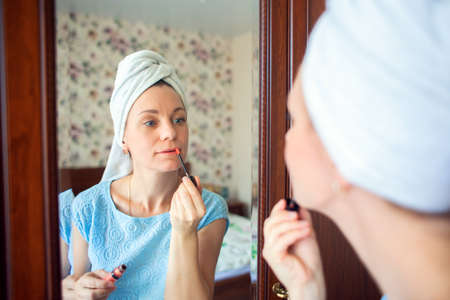 A girl with a towel on her head after a shower paints her lips near the mirror.