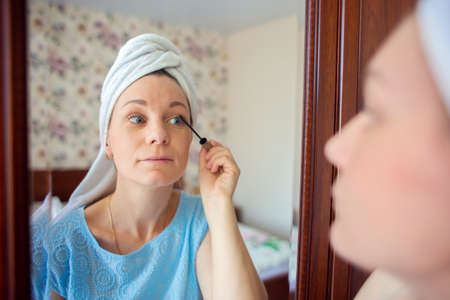 A girl with a towel on her head paints her eyelashes with mascara. Stok Fotoğraf