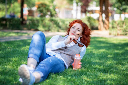 A cute red-haired girl lies in the park on the grass and thinks or dreams about something. Woman walking in a summer park with a bottle of water