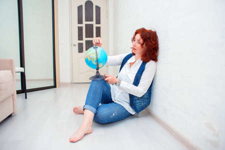 A cute redhead girl sits on the floor and holds a globe in her hands. Woman examines the globe and chooses where to fly on vacation