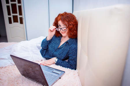 A cute red-haired girl lies on the bed wearing glasses and works on a laptop. Special goggles for computer use
