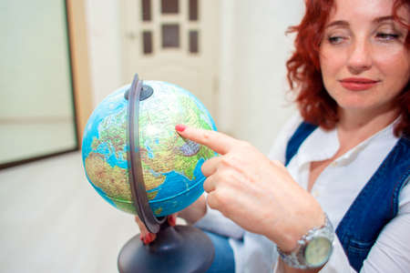 The girl sits on the floor and holds a globe in her hands. Woman points her finger at some place on the globe close-up. Reklamní fotografie