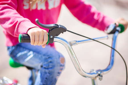 Children's bicycle handlebar with hand brake. The child holds the handlebars of the bike. Healthy lifestyle concept