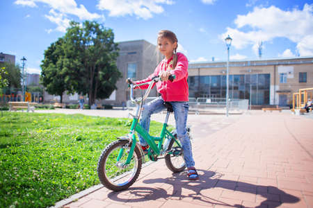 Girl rides a child's bike in a summer park