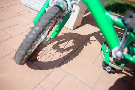 Children's bicycle wheel and its shadow on the paving stones. Carved shadow from the spokes of a bicycle wheel.