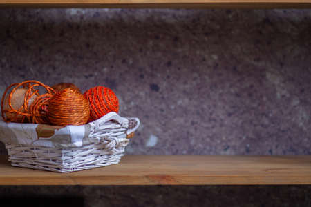 A wicker basket with orange balls of thread or rope folded into it. The handmade basket is on the shelf