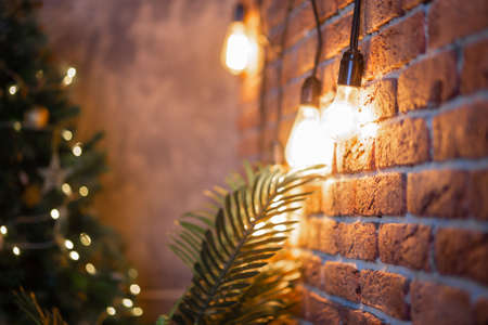A brick wall with a burning light bulb that creates coziness and New Year's mood. Garland Reklamní fotografie