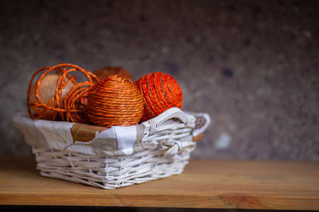 Wicker basket with orange balls of thread or rope folded into it
