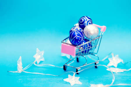Blue Christmas balls are stacked in a small shopping cart. Christmas preparations Reklamní fotografie