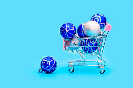 Blue Christmas balls are stacked in a small shopping cart. Christmas shopping