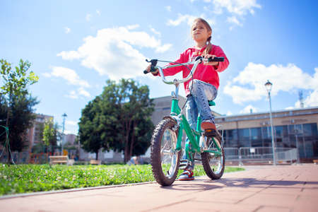 A girl in ripped jeans rides a bicycle in the park. Bottom view Stok Fotoğraf