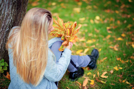 A beautiful girl in a gray cardigan sits on the grass in the park and holds a bouquet of autumn yellow leaves in her hands