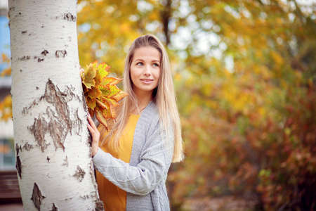 A girl in a gray cardigan and a yellow dress collects autumn leaves in the park Reklamní fotografie