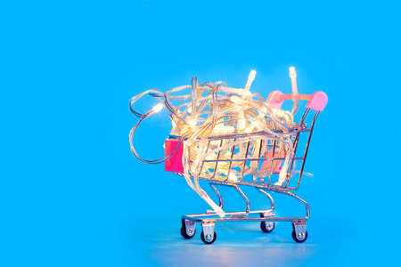 A small shopping cart full of Christmas lights. Preparing for Christmas