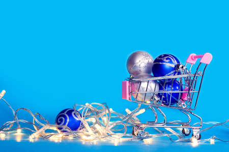 Christmas tree balls and christmas garlands lie in a shopping cart