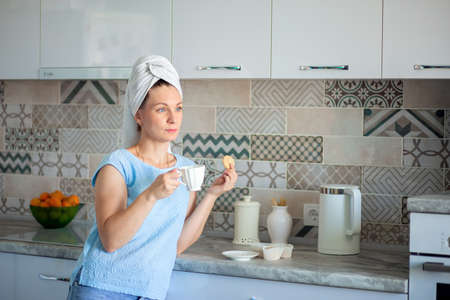 A woman took a shower in the morning and drinks coffee with a towel on her head. breakfast in the kitchen