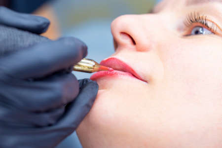 The process of applying permanent makeup on the lips with a tattoo machine close-up