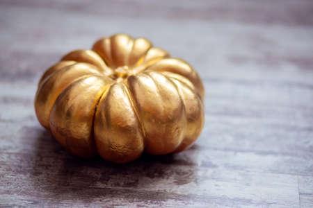 Top view of a large pumpkin painted gold. Postcard for Halloween. Autumn symbol Stok Fotoğraf