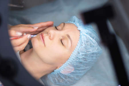 Preparation for permanent lip makeup. Drawing the contour of the lips for tattooing. Woman makes a tattoo on her face
