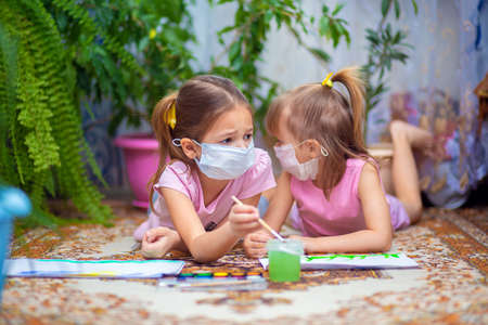 Two girls in protective medical masks paint with paints lying on the floor at home or in kindergarten. Children in self-isolation or quarantine
