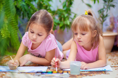 Two girls paint with paints lying on the floor at home or in kindergarten. Children's creativity