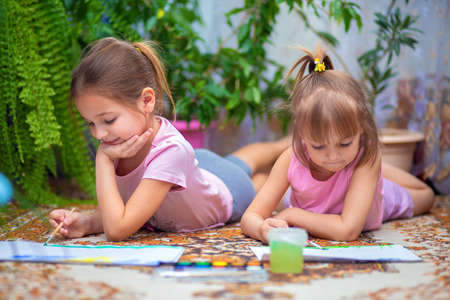 Two girls paint with paints lying on the floor at home or in kindergarten. Home leisure