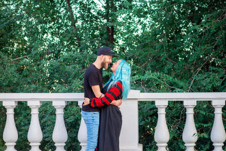 A woman with blue hair hugs her young man with a beard while walking in a city park Stok Fotoğraf