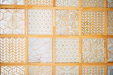 Wooden background in the form of many squares with various sawn patterns