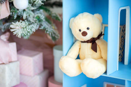 Cute teddy bear sitting in the dollhouse under the christmas tree