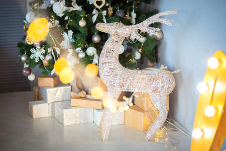 Festive decorative deer stands near the christmas tree in the room Stok Fotoğraf