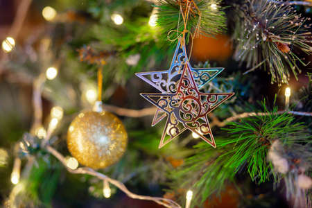 gold star hanging on the branch of the Christmas tree. Christmas tree decoration Stok Fotoğraf